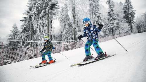 Little brothers skiing together on a beautiful winter day