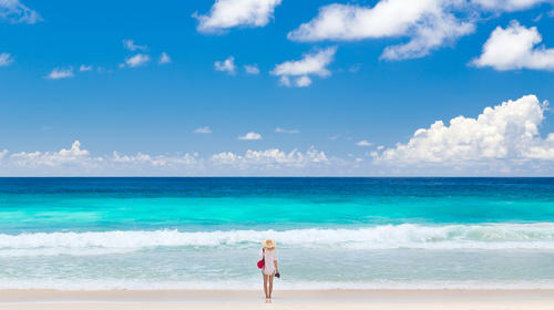 Woman enjoying picture perfect beach on Mahe Island, Seychelles.