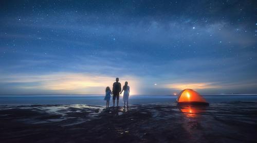 在广西的海边看日落的一家三口
