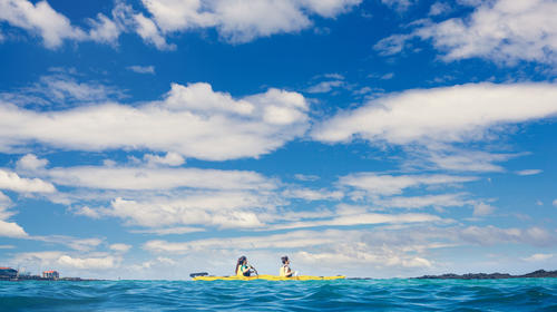 Photography Of Two Young Women Riding A Kayak On The Sea