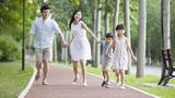 快乐的年轻家庭在公园嬉戏